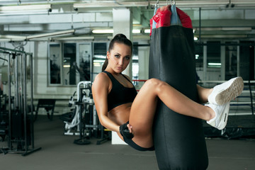 Sexy model posing jumped on punching bag