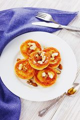 Fritters of cottage cheese with honey and nuts on a white plate