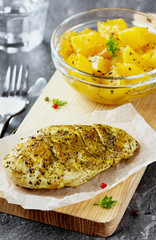 Chicken fillet on a wooden board with a garnish from pumpkin