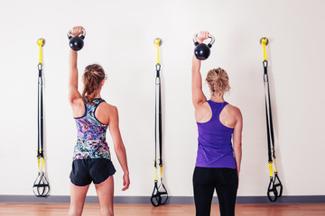 Women doing shoulder press with kettlebells