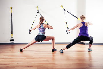 Two women working out with straps