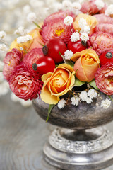 Bouquet of roses and chrysanthemums in vintage silver vase
