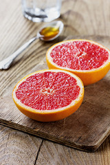Grapefruit with honey on a rustic wooden table