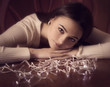 beautiful woman sitting at table with Christmas light garland