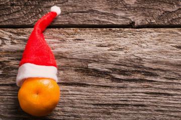 mandarin orange in a Christmas hat on orange background