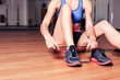 canvas print picture - Woman tying shoes in the gym