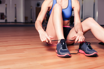 Woman tying shoes in the gym