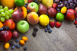Mixed fresh Fruits on the  wooden background  with water drops