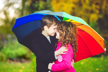 Little girl and boy hiding under an rainbow umbrella from the ra