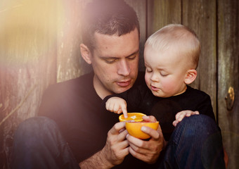 Father and son eating oranges