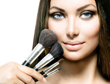 Fototapety Beauty Girl with Makeup Brushes. Applying Makeup