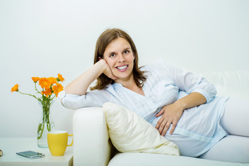 Pregnant woman lying on sofa
