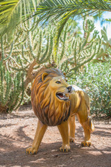 Artificial lion in national park. Toy for kids.