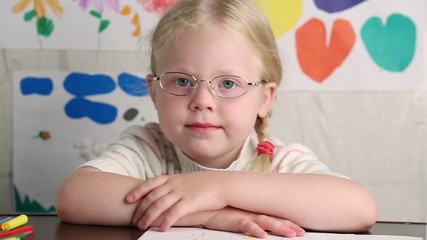 little girl in glasses sits at a school desk - dolly shot