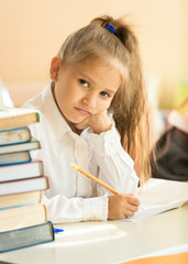 upset girl writing test in classroom and looking at camera