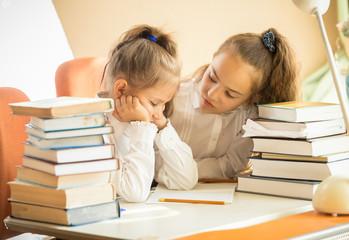 two cute girls being sad of hard homework