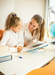 cute daughter doing homework with mother