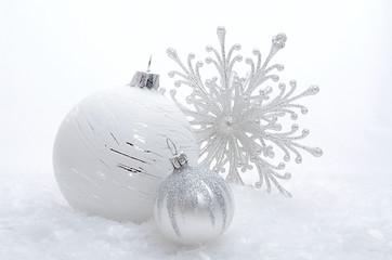 Silberne Weihnachtkugeln mit Eiskristall im Schnee