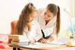 beautiful mother helping daughter doing homework
