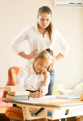 mother watching at daughter doing homework