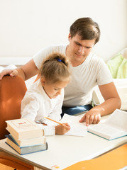 man pointing on mistake at daughters notebook