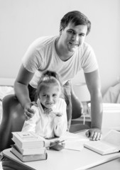 Monochrome portrait of daughter doing homework with father at ho
