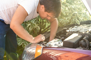 man looking at open car hood and fixing engine