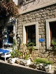 Altbau mit Fassade aus Naturstein und Blumenkästen in Alacat