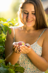cute smiling woman holding tenderly red apple in hands at garden