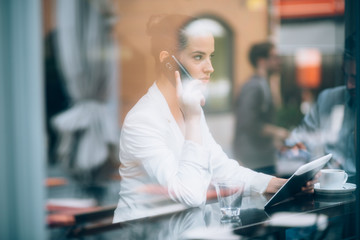 Busy businesswoman talking on phone and using tablet computer in