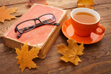 Fototapety Autumn leaves, book and cup of tea on wooden table in studio
