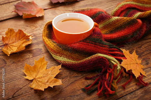 Autumn leaves, book and cup of tea on wooden table in studio poster