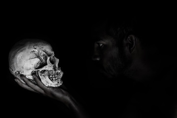 Man in shadow stare human skull that hold in hand
