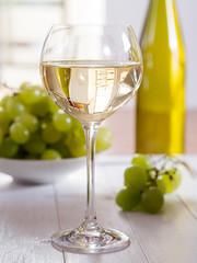 Ein Glas Weisswein mit Weintrauben