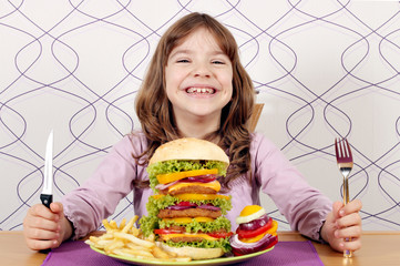 happy little girl with big hamburger on table