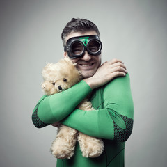 Smiling superhero cuddling a teddy bear
