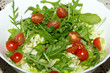 Heap of ruccola, lettuce leaves and cherry tomatoes