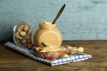 Tasty sandwich and jar with fresh peanut butter