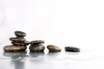 Spa stones in water on table on light background