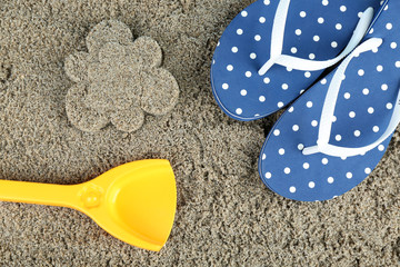 Flower-shaped wet sand and flip flops, close-up