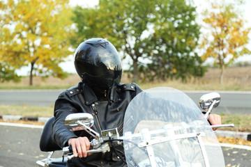 Biker man in black helmet sits on bike
