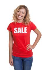 Stehende blonde Frau im Sale-Shirt