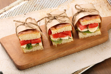 Focaccia sandwich with mozzarella basil and tomato on a chopping