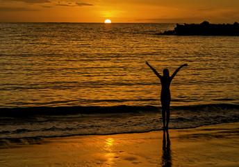Девушка сидит на берегу и смотрит на океан