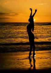 Девушка танцует на берегу океана на закате
