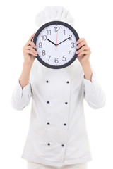 young woman chef in uniform holding office clock behind her face