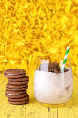 Milk cocktail with chocolate cookies on yellow background