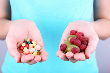 Woman holding berries and pills on grey background