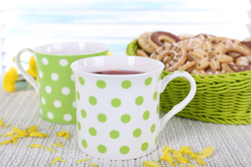 Two polka dot cups of tea with biscuits