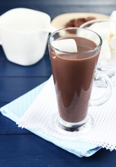 Chocolate drink with marshmallows in mug, on wooden background